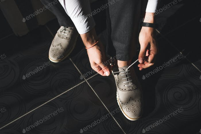 Men wearing grey leather classic shoes, black trousers and white shirt, business style