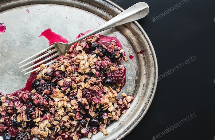 Oat granola with fresh berries on a silver dish with a fork on b