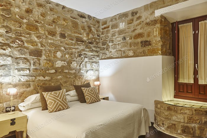 Bedroom with stone walls. Comfortable modern hotel room. Interior architecture