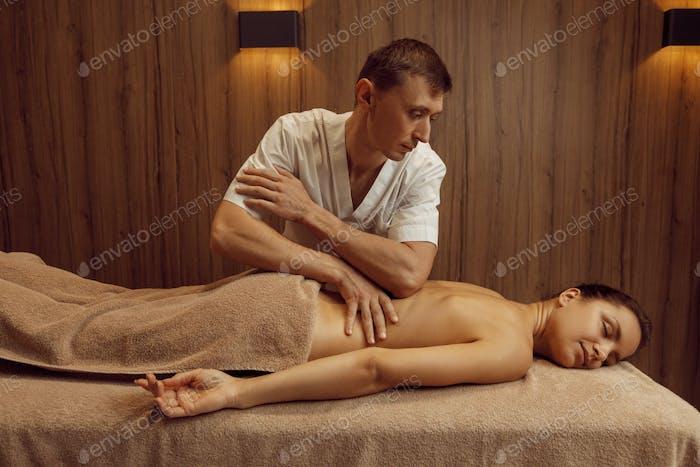 Male masseur rubbing hands to slim woman