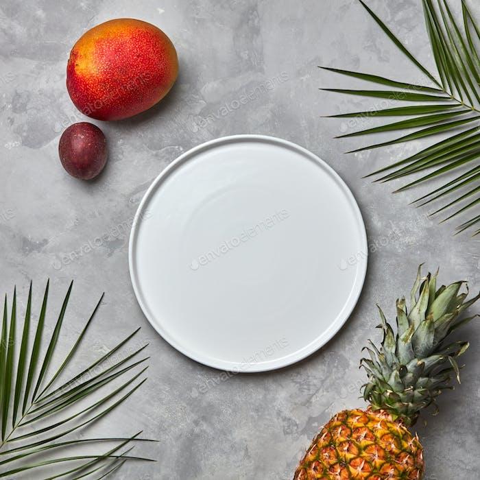 Zusammensetzung aus einem leeren weißen Teller mit grünen Palmblättern, Ananas, Mango und Passionsfrucht auf einem