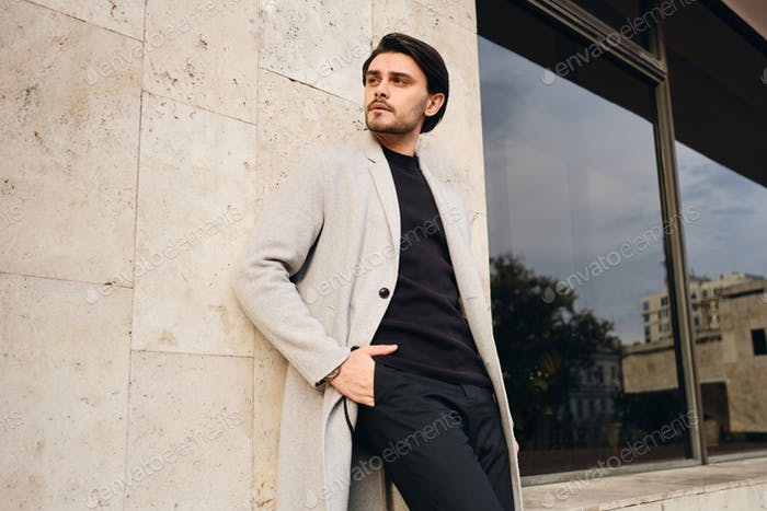 Young handsome stylish man in coat with hands in pockets intently looking away outdoor