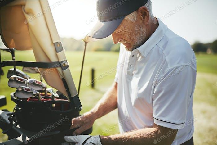 Senior man looking through his golf club bag