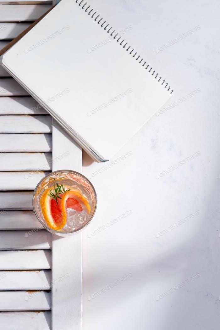 Cold summer homemade cocktail in a glass with slice of grapefruit and and paper note book on a white