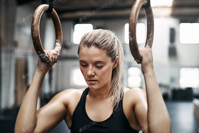 Focused young woman exercising on rings at the gym
