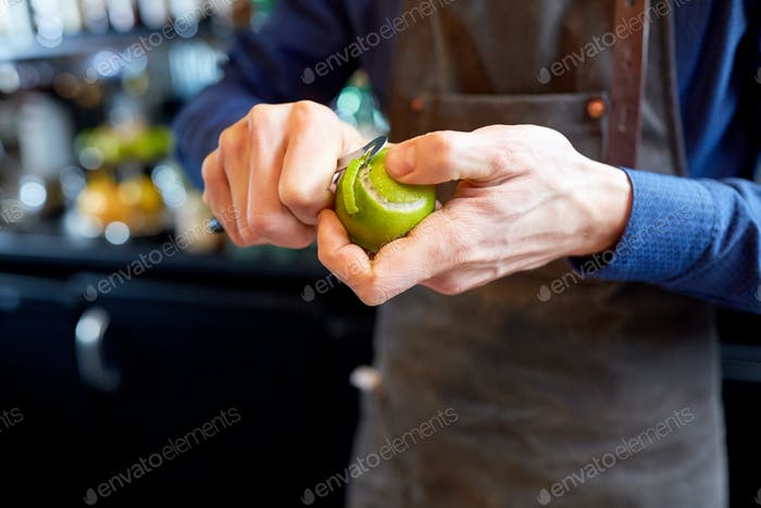 bartender removing peel from lime at bar
