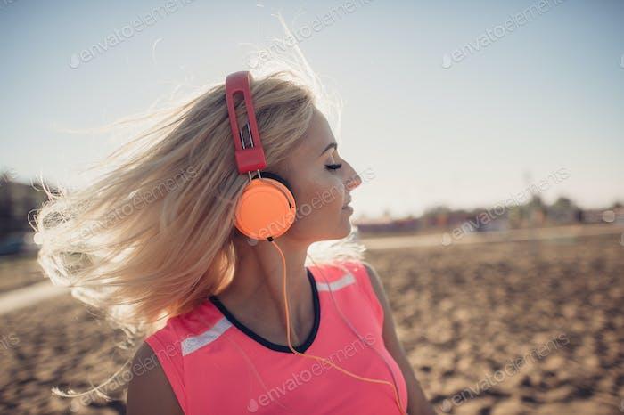 Porträt von jungen schönen Frau Musik am Strand zu hören. Nahaufnahme Gesicht der lächelnden blonde Frau