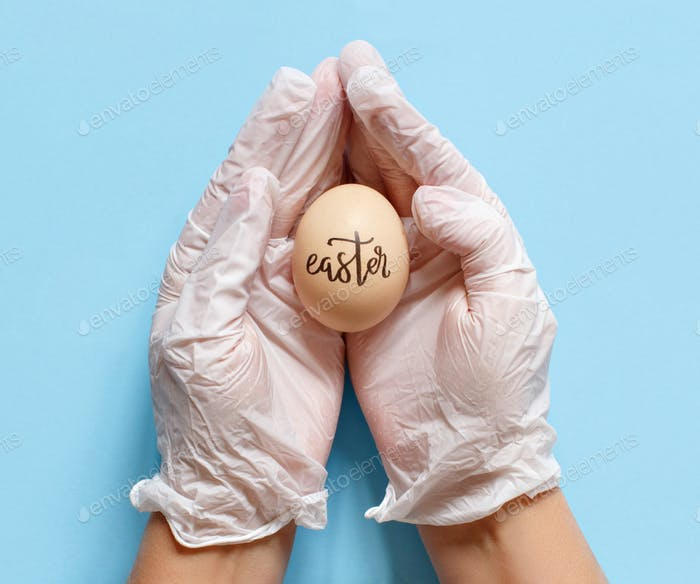 Hands in gloves keeping egg with inscription EASTER over blue background