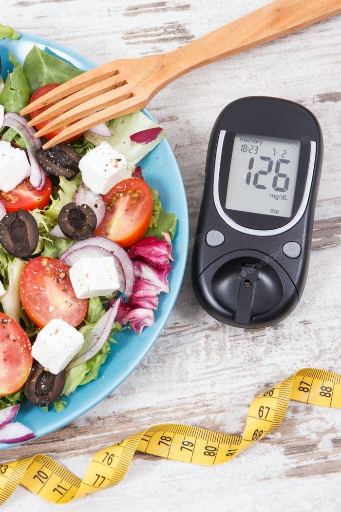 Glucometer for checking sugar level, tape measure and fresh greek salad