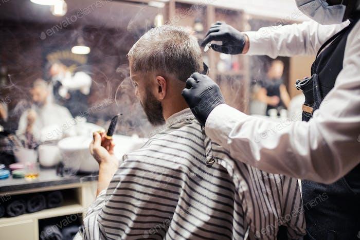 Hipster Mann Kunde Besuch haidresser und Friseur im Friseurladen, eine Pfeife rauchen.