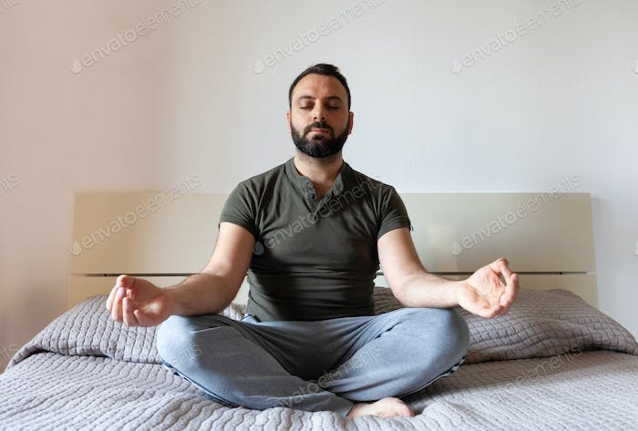 Man relaxing with yoga in bedroom.