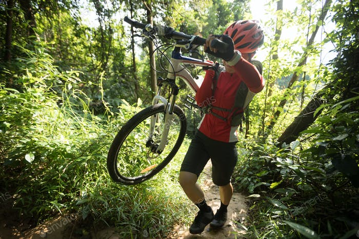 Woman cyclist carrying a Mountain Bike climbing on mountain forest