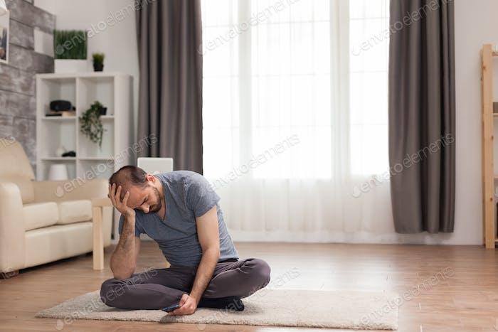 Bored man sitting on carpet in living room
