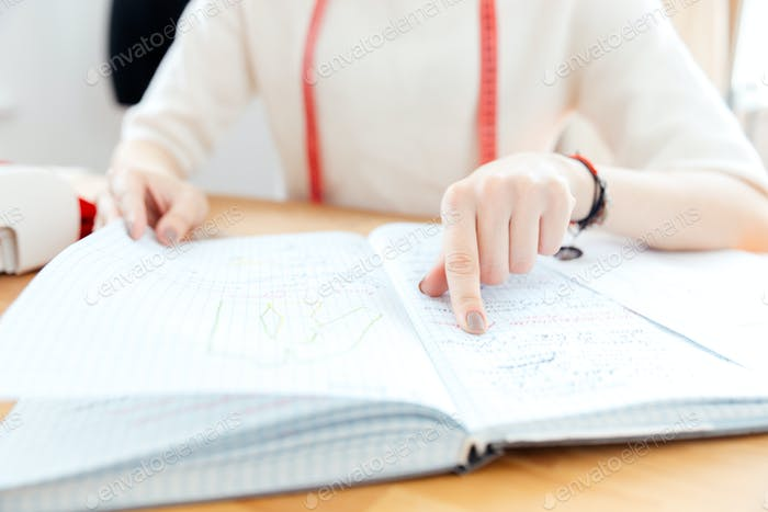 Young woman seamstress pointing and reading notes in notebook
