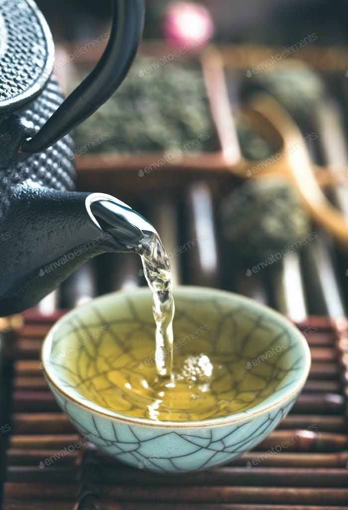 Pouring green tea vertical closeup