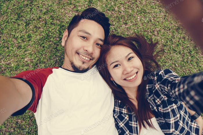 Couple taking a selfie in the grass