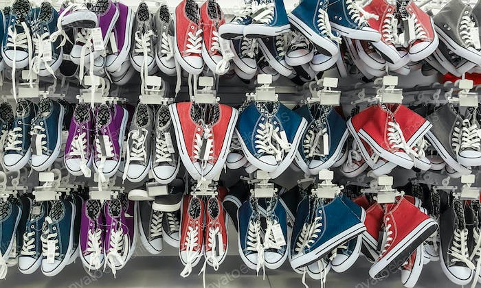 Many pair of sneakers in a store.