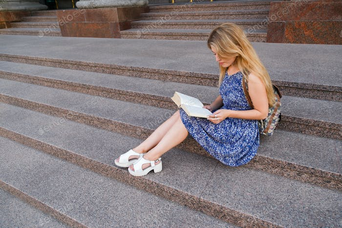 Young woman student sitting on the steps