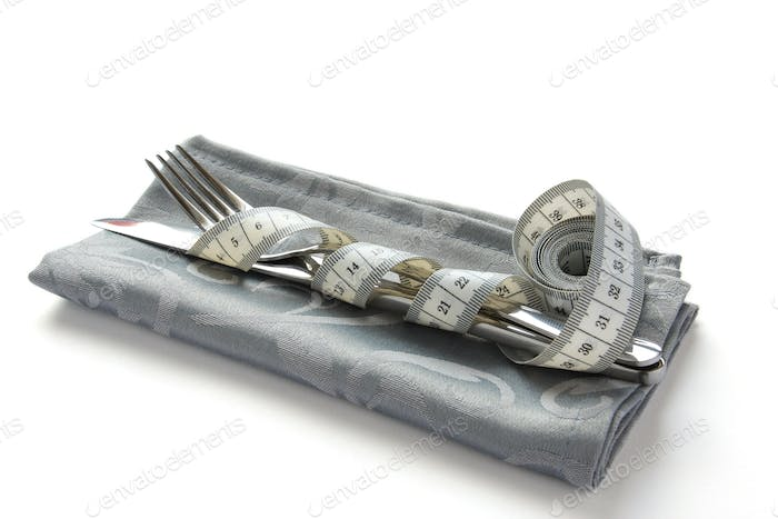 Measuring tape wrapped around knife and fork over white