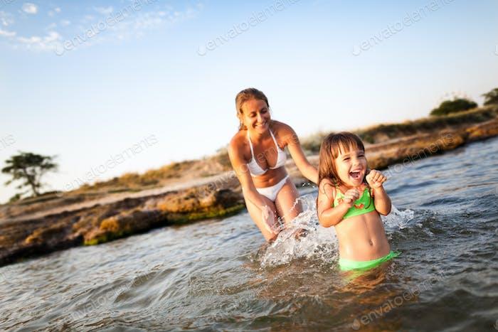 Молодая блондинка в белом бикини и маленькая счастливая девушка весело провести время в морской воде с каменистым пляжем в
