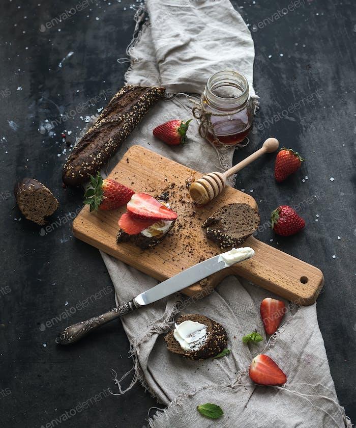 Breakfast set. Black baguette toasts with fresh strawberries, honey