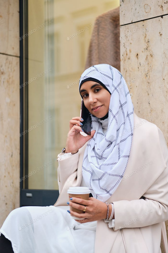 Young attractive Arabic woman in hijab with coffee to go talking on smartphone on city street