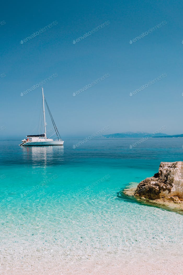Beautiful azure blue lagoon with sailing catamaran yacht boat at anchor. Pure white pebble beach