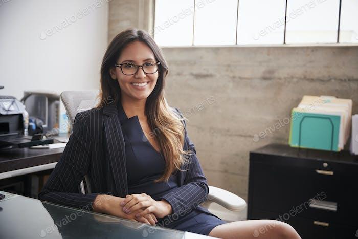 Junge Frau in Brille sitzt am Schreibtisch lächelnd Kamera