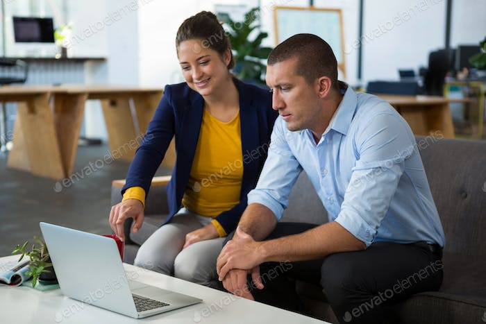 Business colleagues discussing over laptop