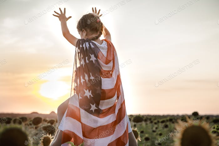 a girl holds an American flag at sunset .