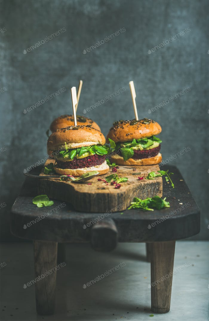 Healthy vegan burger with beetroot-quinoa patty and arugula on table