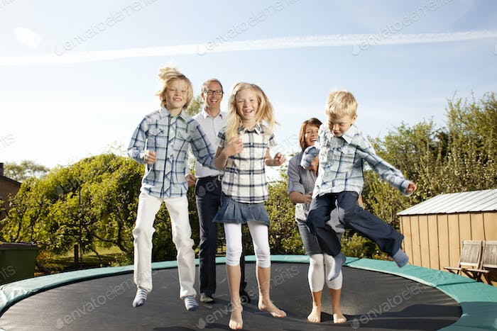 Cheerful family jumping on trampoline in back yard against sky
