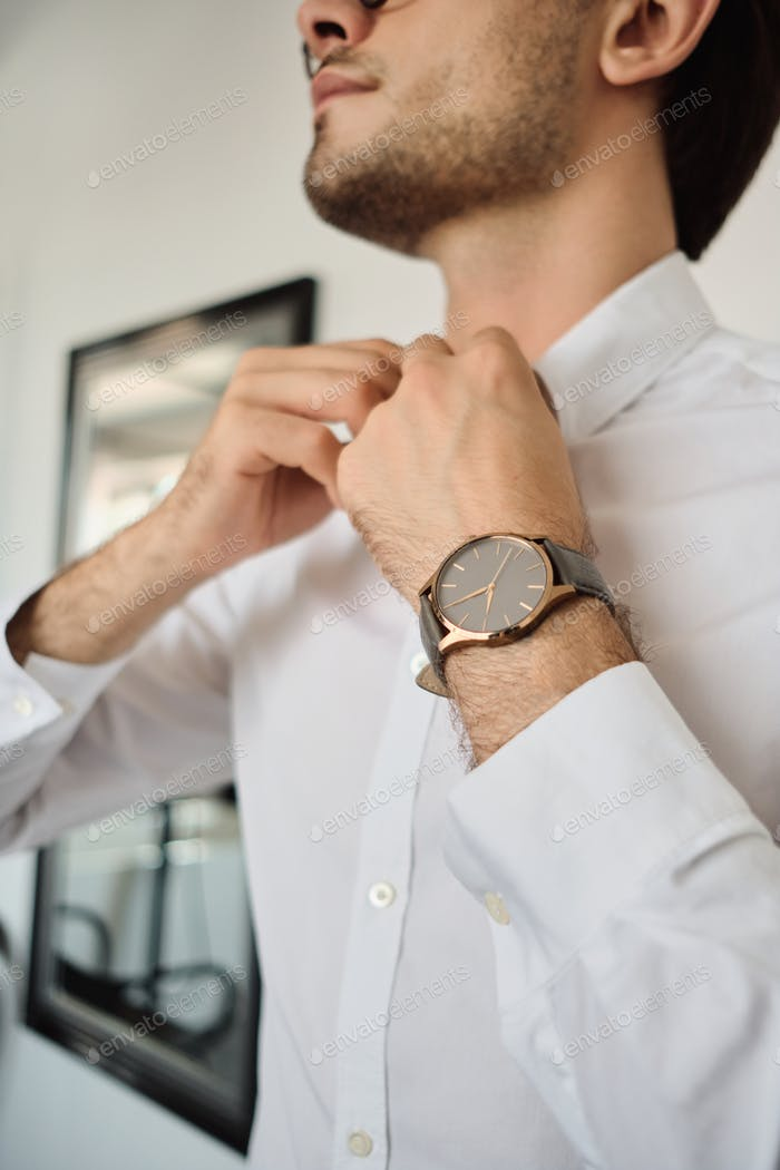 Close up photo of young attractive brunette man in white shirt with watch at modern home