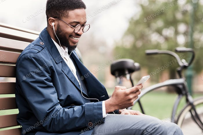 Always in touch. African businessman using smartphone outdoors