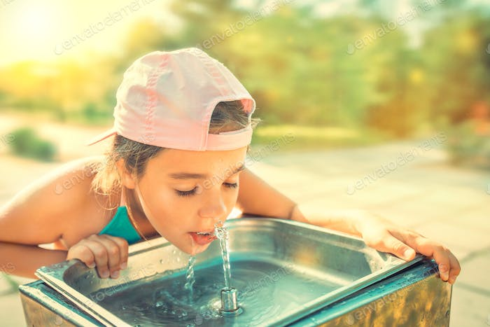 Cute thirsty girl drinks water from drinking sink