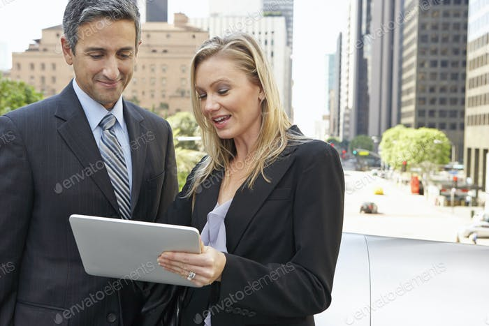 Businessman And Businesswoman Using Digital Tablet Outside