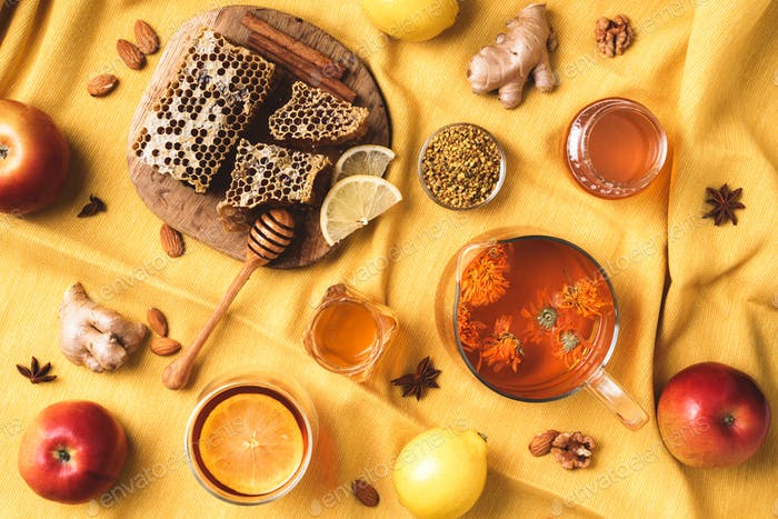 Autumn harvest concept. Set of honey and bee products, apple, lemon, calendula tea, spices on yellow