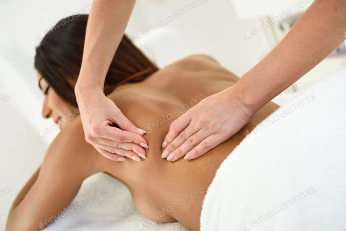 Arab woman receiving back massage in spa wellness center.