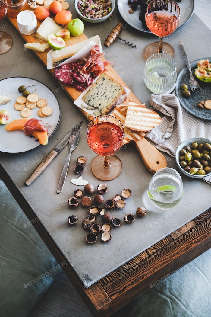 Picnic with rose wine, cheese, charcuterie, appetizers and fresh fruits