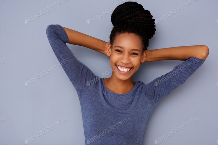 cheerful young black girl with hands behind head smiling on gray background
