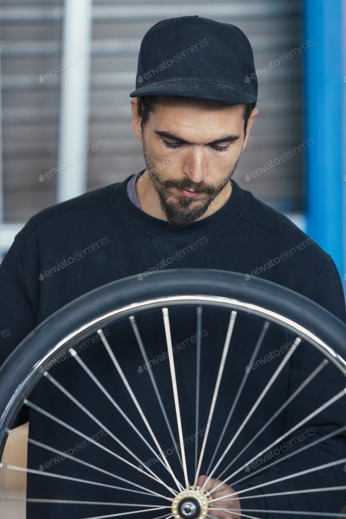 Craftsman looking down on bikes wheel