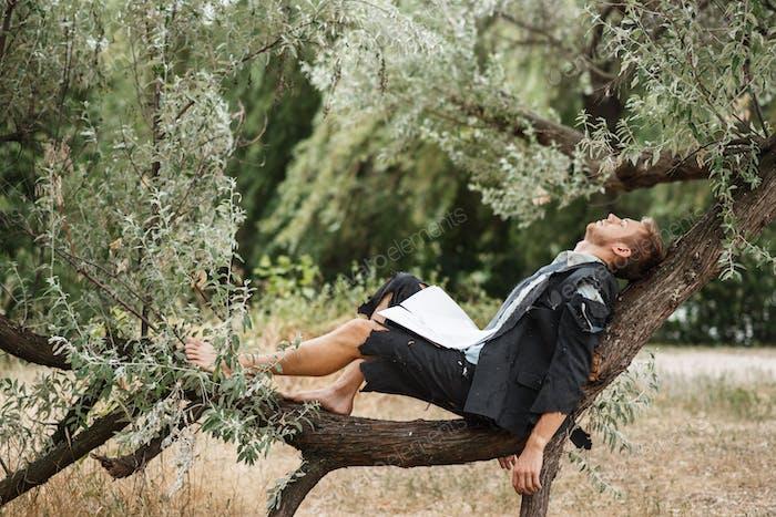Businessman resting on the tree, desert island