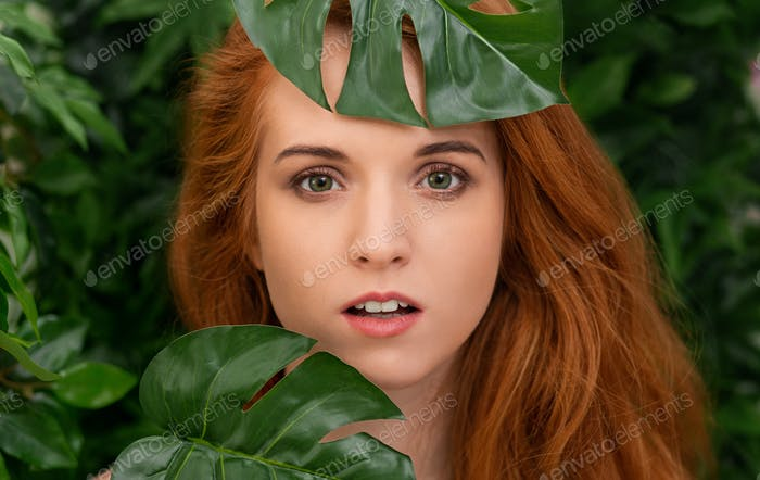 Sensual portrait of redhead woman with green leaves