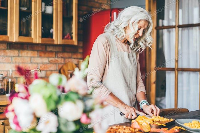 Alte Dame mit langen lockeren grauen Haaren knetet Teig unter frischen Produkten zu Hause.