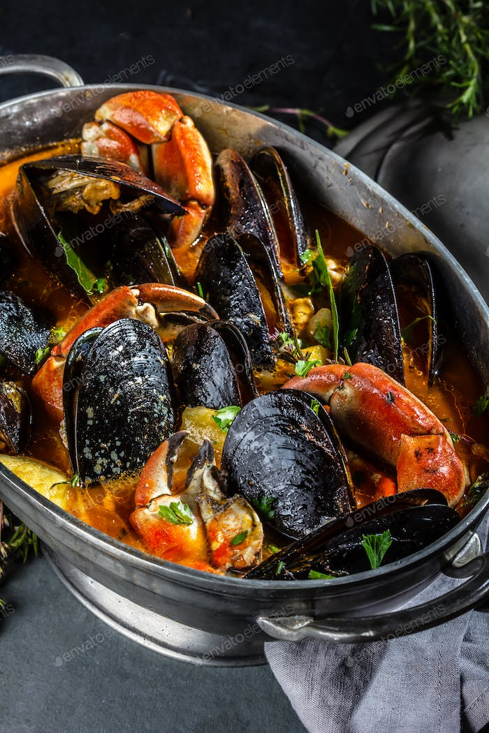 Seafood mussels crabs soup in metal pot