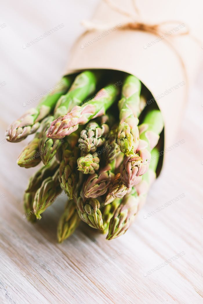 Bunch of fresh uncooked asparagus on a cutting board. The concept of healthy food.