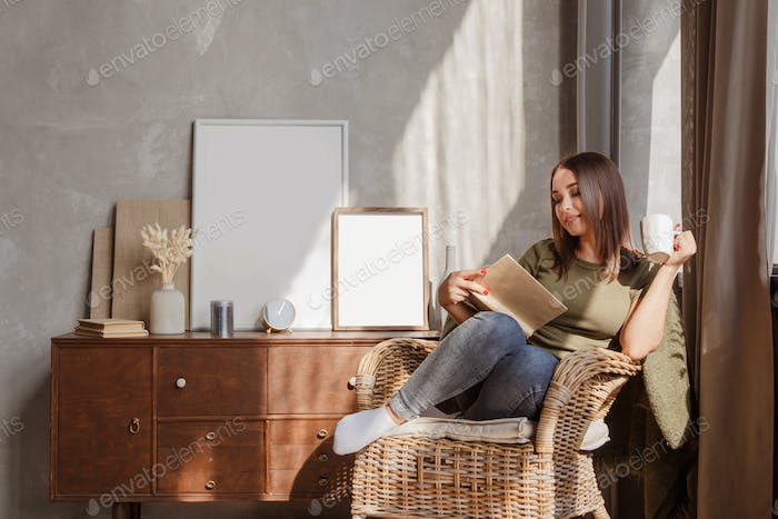 Young woman reading a book and holding cup of tea or coffee sit in rattan wicker armchair