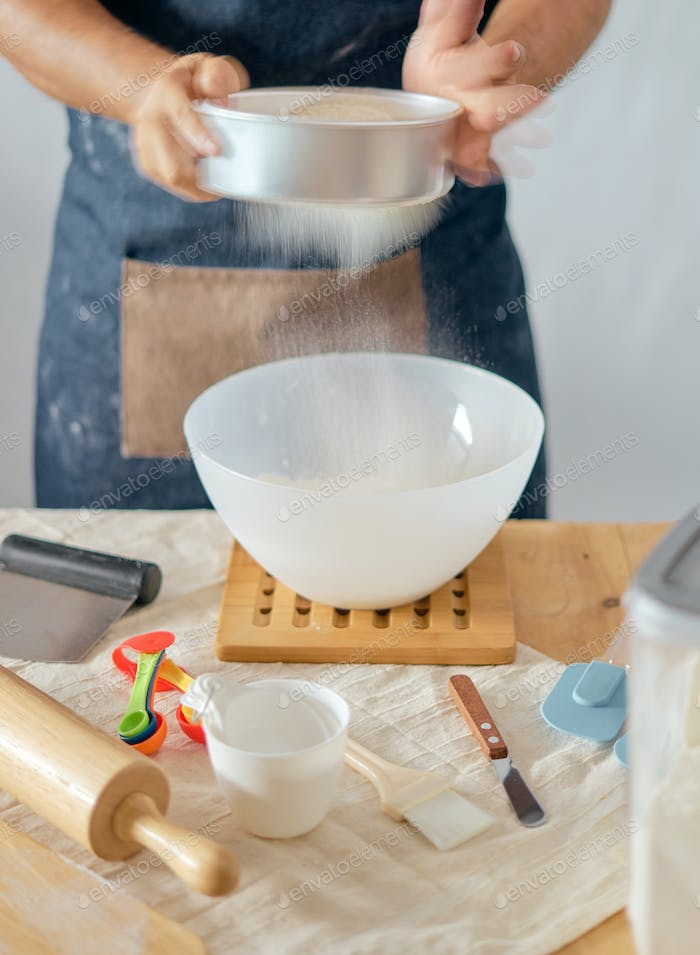 Baker sieving flour to mixing bowl