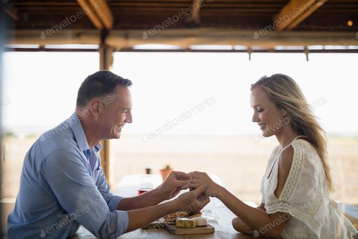 Smiling man wearing engagement ring to woman