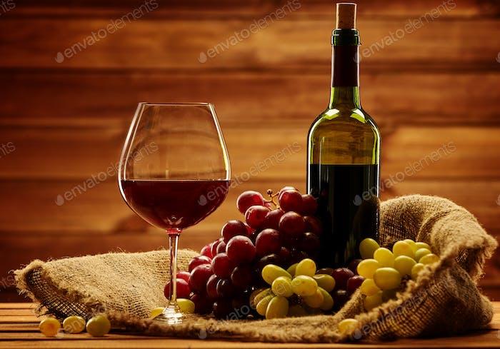 Botella de vino tinto, copa y uva en cesta en interior de De madera